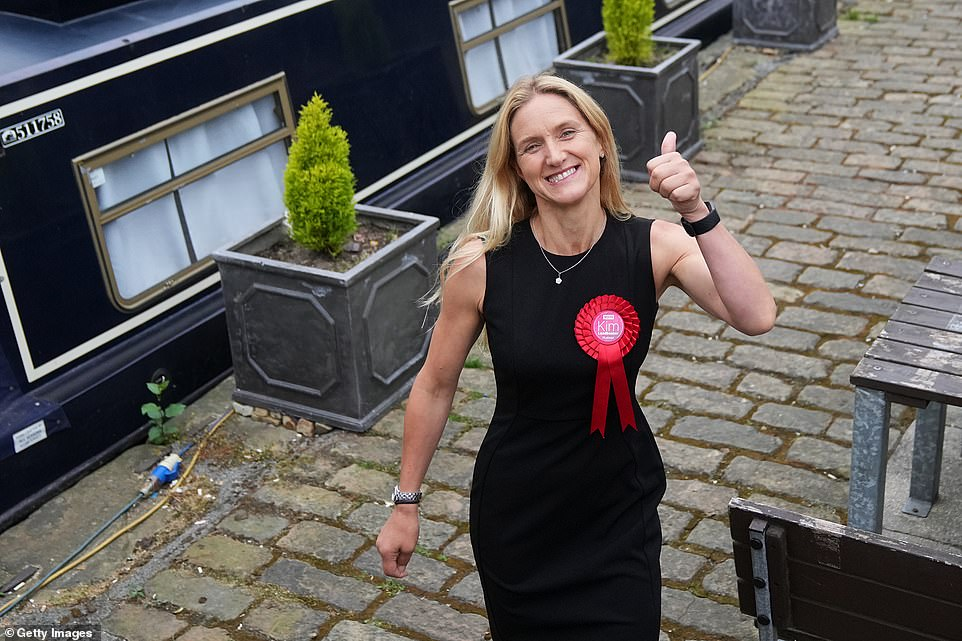 Kim Leadbeater of the Labour Party sticks up her thumb as she reacts to the media after winning the Batley and Spen by-election this morning