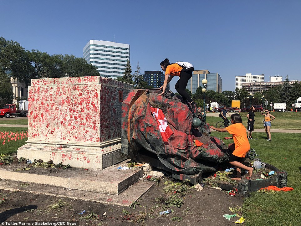 A gigantic statue of Queen Victoria has been torn down and daubed in red paint in Winnipeg, Manitoba, on Canada Day as a backlash over the country's colonial history ramps up