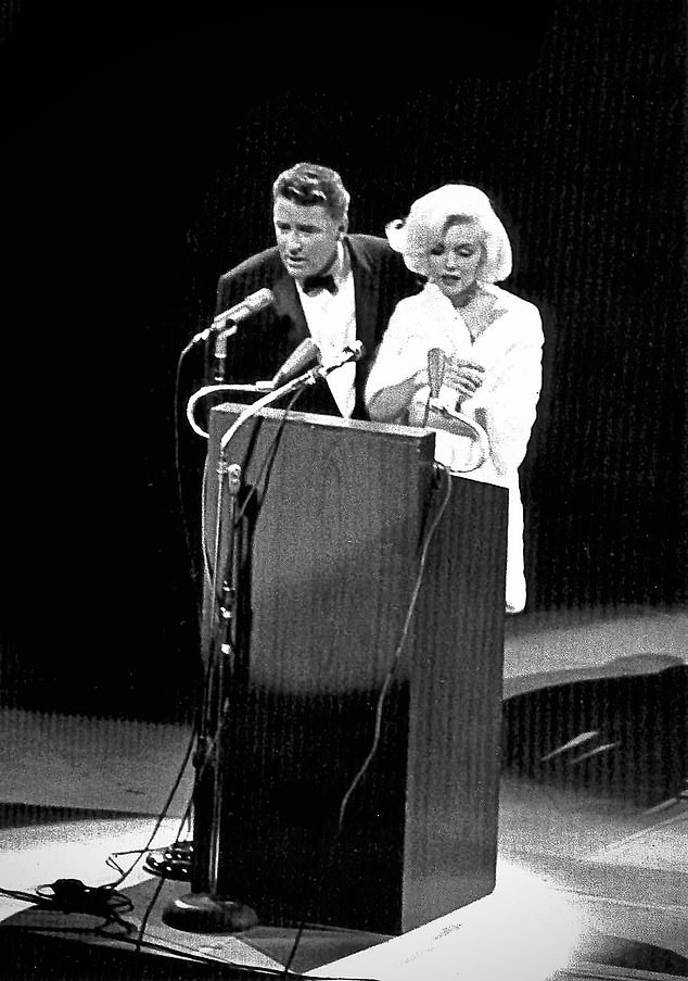 JFK's birthday surprise: Peter Lawford introduces Monroe — before her wrap fell away to reveal her skin-tight dress. One journalist described it as 'making love to the President in the direct view of 40 million Americans'.