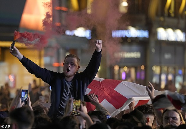 Thousands of England supporters have taken to the streets to celebrate England's win against Ukraine. Pictured: An unmasked fan atop his friend's shoulders in Leicester Square, London
