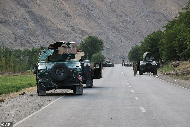 Afghan soldiers pause on a road at the front line of fighting between Taliban and Security forces, near the city of Badakhshan, on Sunday