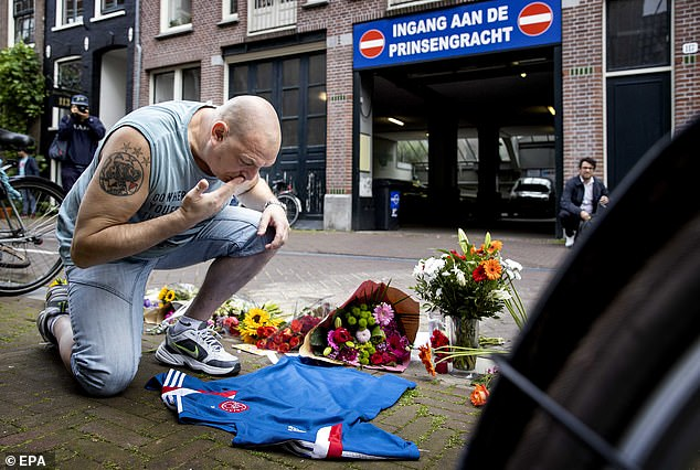 People leave flowers, candles and messages of support to Dutch crime reporter Peter R. de Vries at the spot where he was shot in Amsterdam on Tuesday night