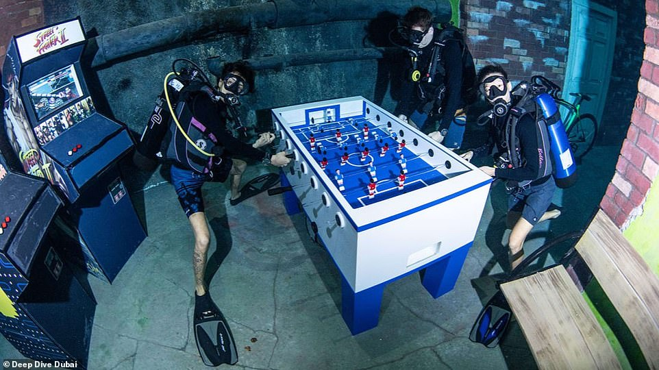 Divers are pictured enjoying the underwater arcade playing table football among other games in the depths of the underwater amusement park