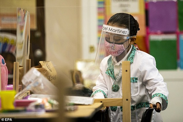 The CDC issued new guidance on Friday calling for K-12 schools to fully reopen in fall 2021. Pictured: A kindergarten student at Resurrection Catholic School in Los Angeles, California, February 2021