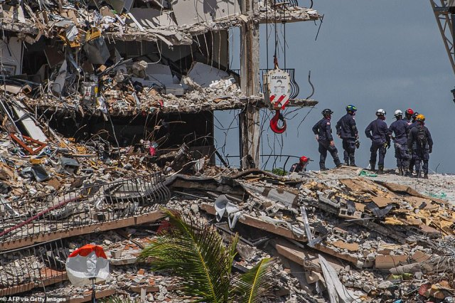 Rescuers are seen searching through the debris on June 27. The death toll is now at 86