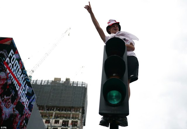 An England fan climbs on top of traffic lights outside the ground ahead of the Euros final at Wembley Stadium
