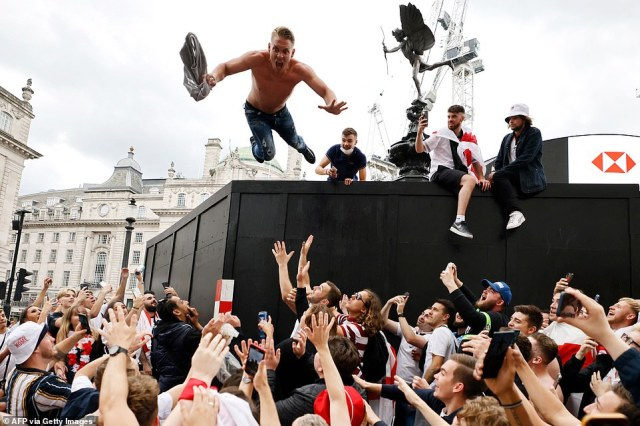 A man jumps from the Shaftesbury Memorial Fountain in Piccadilly Circus ahead of the UEFA EURO 2020 final football match