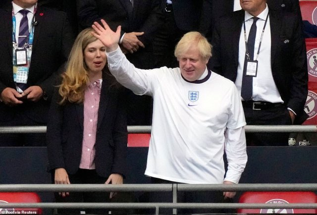 Boris Johnson with wife Carrie waves from the stands