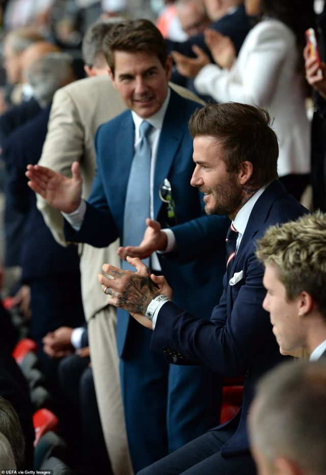 Smart: David and Tom both wore suave navy suits as they watched the match from the stands on Saturday night