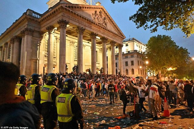 Police officers monitor the wild England supporters standing outside St. Martin-in-the-Fields church on the edge of Trafalgar Square