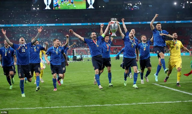 Italy's Giorgio Chiellini and Leonardo Bonucci carry the trophy and celebrate with team-mates after winning the penalty shoot-out after the UEFA Euro 2020 Final at Wembley