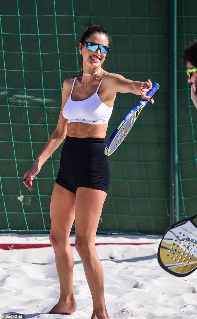 Ripped! The longtime supermodel flashed her ripped abs as she showed off her beach tennis technique