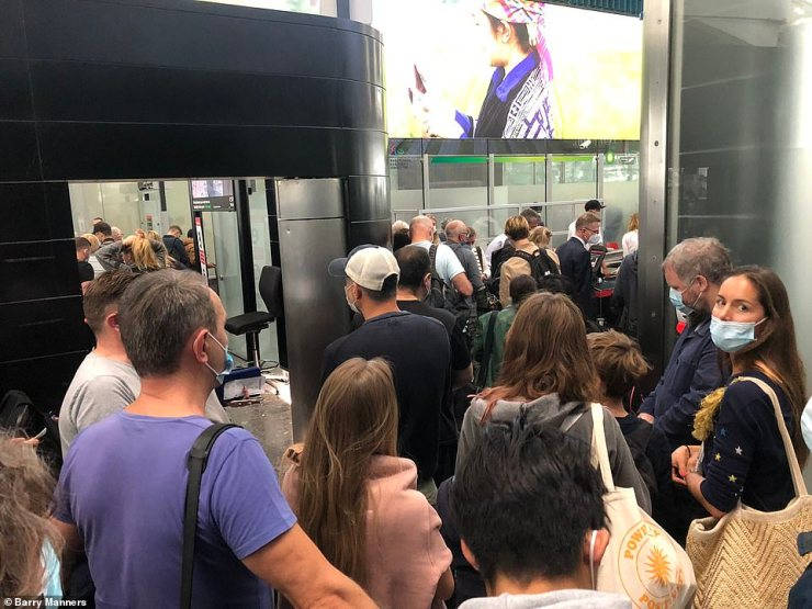 People wait in the departures hall at London Heathrow Airport Terminal Five this morning