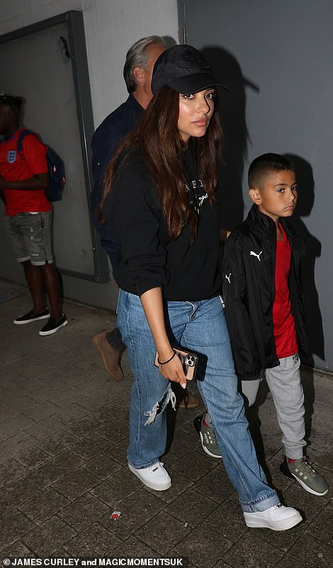 Stylish: Jade was rocking ripped jeans, a hoodie and baseball cap for the game