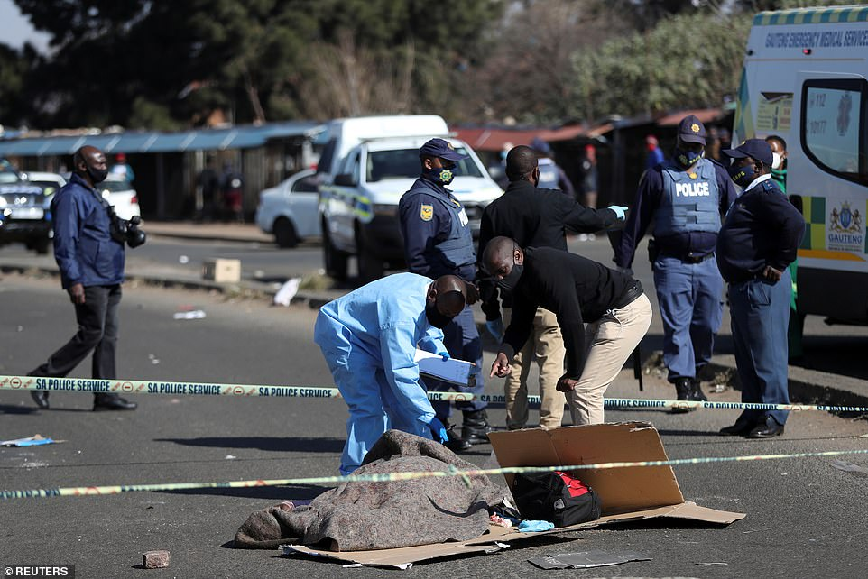 Police and forensic experts inspect the body of a man shot dead inKatlehong, South Africa, amid rising violence over the jailing of ex-president Jacob Zuma