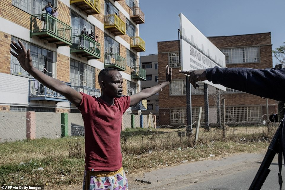 A protester gestures as he is confronted by South African police in a suburb of Johannesburg during violence at the weekend