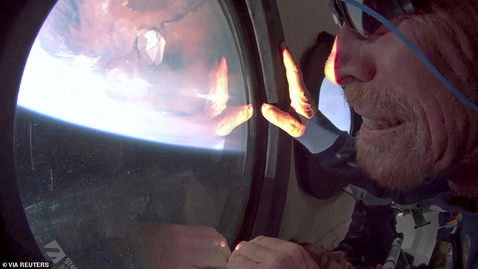 Branson looks out the window at Earth in zero gravity on board Virgin Galactic's passenger rocket plane VSS Unity after reaching the edge of space