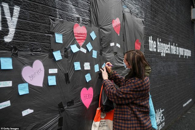 Local residents put messages of support on the plastic that covers offensive graffiti on the vandalised mural of Manchester United striker and England player Marcus Rashford