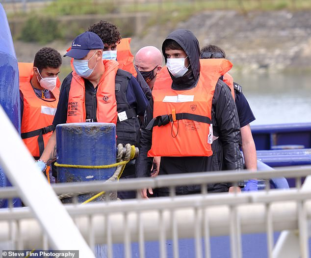 A group of migrants arrive to Dover Marina in Kent today after making the treacherous journey across the English Channel