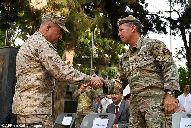 General Kenneth McKenzie (left), the head of US Central Command, shakes hands with General Austin 'Scott' Miller, US top commander of coalition forces in Afghanistan, during an official handover ceremony at the Resolute Support headquarters in Kabu ltoday