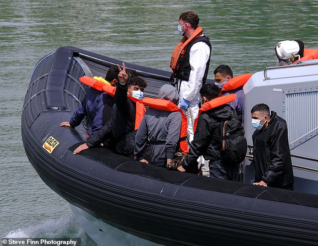 A group of migrants arrive to tr Around 10 boats are thought to have attempted the treacherous trip across the world's busiest shipping route today as the number of vessels left eerily floating at the harbour in Dover continues to rise.