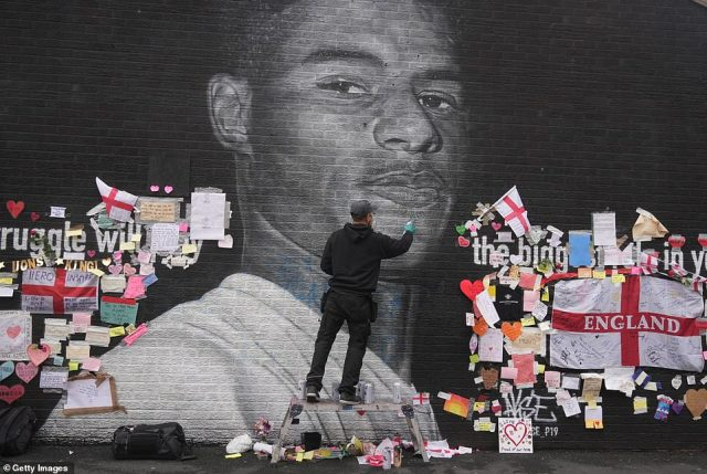 The artist known as AKSE_P19, who painted the mural of Rashford, which is displayed on the wall of a cafe on Copson Street, Withington, repaints it after it was defaced by vandals