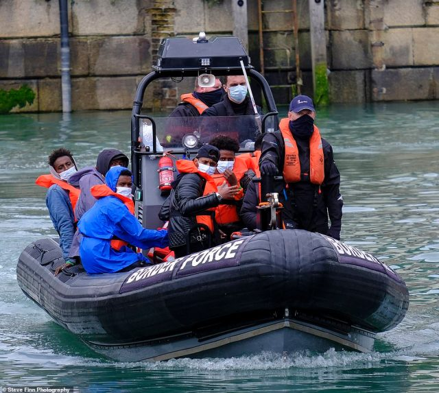 A group of migrants are brought into harbour on the beach at Dungeness, along the coast of Kent, by the Border Force officials