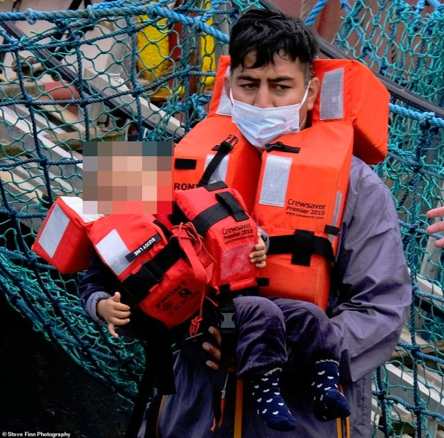 A Border Force officer carries a toddler from a migrant boat in Dover, Kent