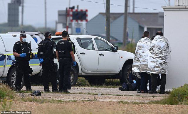 Police officers at the scene as a group of migrants arrive to Dungeness after crossing the Channel