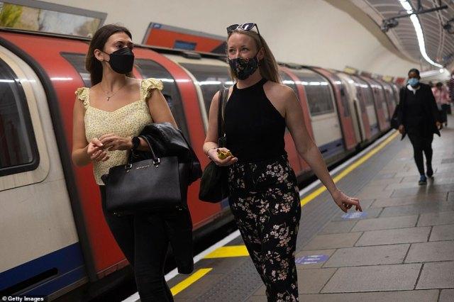 Women wearing face masks walk through Notting Hill Gate station on July 13, 2021