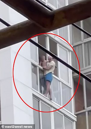 Terentyev stands on the window ledge with his son