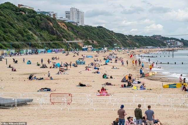 An 80F five-day heatwave set to hit tomorrow will make the UK hotter than Crete - after torrential rain overnight lead to 'biblical' flash flooding in London. Pictured: People on the beach inBournemouth
