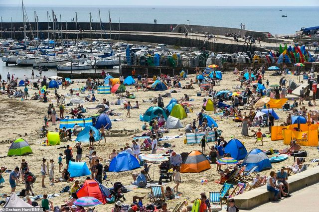 Huge crowds of beachgoers soaked up the sun inLyme Regis, Dorset, as the rain made way for higher temperatures