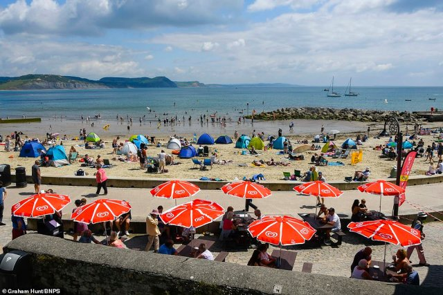 Families and sunbathers flock to the beach at the seaside resort of Lyme Regis in Dorseton an afternoon of scorching hot sunshine