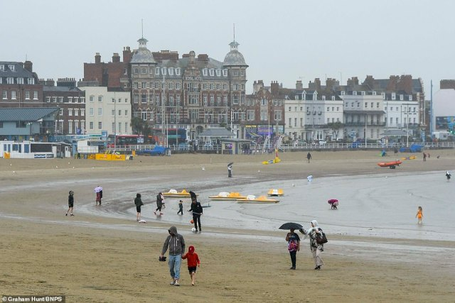 Drivers were told to beware of difficult driving conditions and some road closures due to the heavy rain, while warnings of possible travel disruption across train and bus services were also issued. Pictured: Rainy Weymouth in Dorset