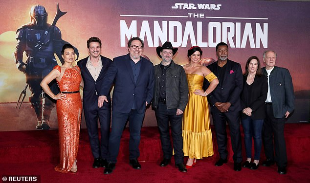 The team: Pedro, second from left, with Creator Jon Favreau (3rd L), President of Lucasfilm Kathleen Kennedy (2nd R), executive producer Dave Filoni (C) pose with cast members (L-R) Ming-Na Wen, Gina Carano, Carl Weathers and Werner Herzog in 2019