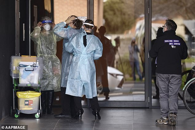 Pictured: Vic Health workers prepare to enter Ariele Apartments in Maribyrnong, Melbourne, on Tuesday