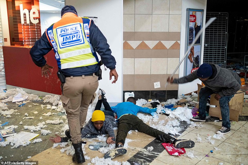 A police officer stands on the arm of a suspected looter while another man wields an iron bar during the violent scenes in Johannesburg on Tuesday