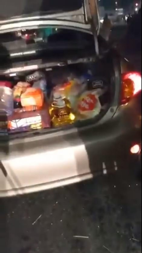 The man's car is seen filled with household supplies including bottles of cooking oil