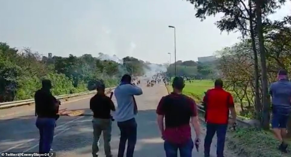In the clip, a line of shop and property owners fired on the rioters from afar before running closer and continuing to shoot, while the crowds protected themselves behind road signs and ran off the road amid the chaos