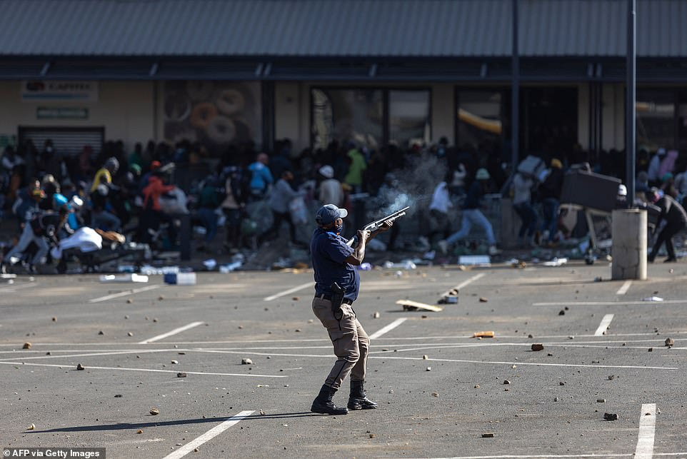 A member of the South African Police Services (SAPS) fired rubber bullets at rioters looting the Jabulani Mall in Soweto on Monday
