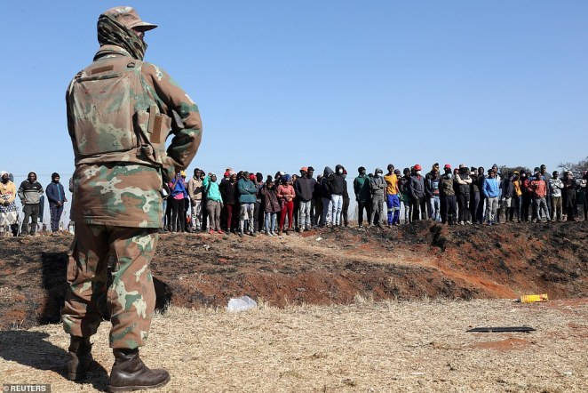 An soldier stands guard as protesters gather in a field inVosloorus, east of Johannesburg, on Wednesday
