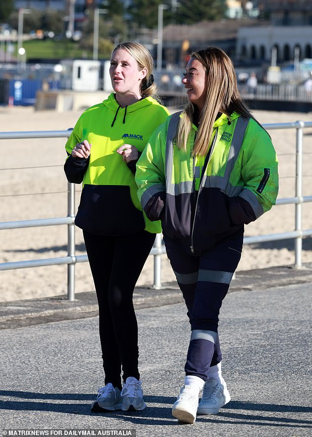 Two pedestrians in hi-vis jackets are pictured walking along the promenade at Bondi Beach in Sydney's eastern suburbs. The NSW government has refused to enforce a time limit on daily exercise