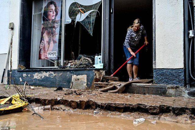 A woman cleans a shop entrance after flooding in the town of Bad Muenstereifel, south of the city of Bonn and located along the banks of the Erft river
