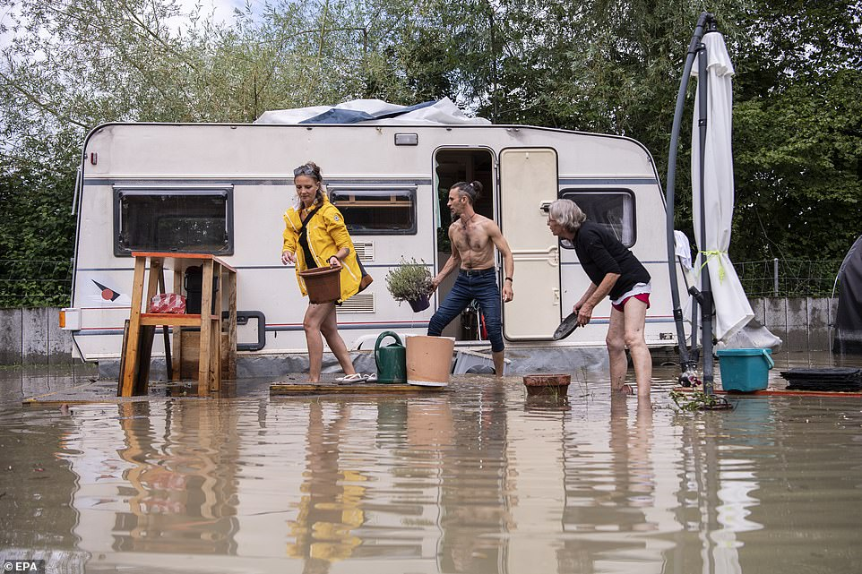SWITZERLAND: People rush to remove their belongings from a flooded campsite inOttenbach after the nearby Reuss river burst its banks amid heavy downpours