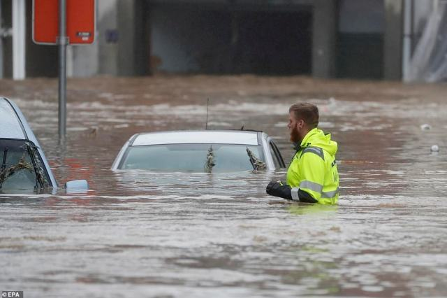 A man wades through the water as flooding affects the area after heavy rains in Ensival, Belgium