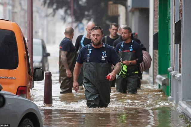 Emergency workers wade through the water as flooding affects the area after heavy rains in Ensival, Verviers, Belgium