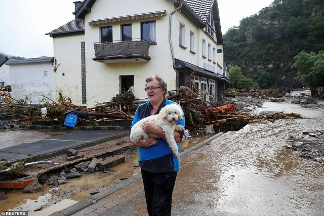A man carries a dog next to debris brought by the flood, following heavy rainfalls in Schuld, Germany