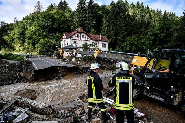 Firefighters begin to repair a damaged road after flooding in Schuld, Germany, to assist with rescue efforts