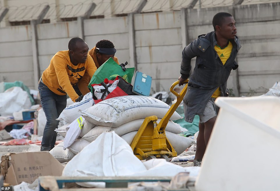 But in some places, looting continued into Thursday. Pictured: people make off with a trolley of bags of rice in Durban